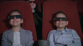Excited kids watching cartoon in 3D movie theater. Childhood concept. Children in 3D glasses watching movie in cinema. Excited kids watching cartoon in 3D movie stock footage