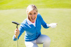 Excited lady golfer cheering on putting green Royalty Free Stock Photo