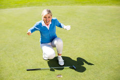 Excited lady golfer cheering on putting green Stock Photography