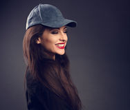 Excited laughing beautiful brunette woman in baseball blue cap w Royalty Free Stock Photos