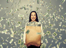 Excited laughing woman holding money. Excited laughing businesswoman standing under dollar's rain and holding big paper bag with money Stock Photos