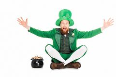 Excited leprechaun gesturing and sitting at pot of gold. Isolated on white Royalty Free Stock Image