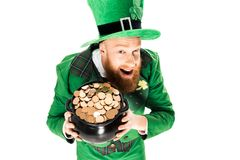 Excited leprechaun in green suit and hat holding pot of gold. Isolated on white Royalty Free Stock Images