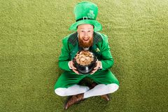 Excited leprechaun with pot of gold sitting. On green grass stock photo