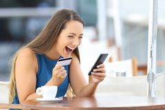 Excited on line buyer paying with credit card. Using a smart phone sitting in a bar terrace Royalty Free Stock Image