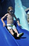 Excited Little Boy. This is a picture of a very excited and happy little boy sliding down a water slide at a water park Stock Photography
