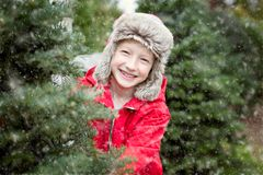 Kid at winter. Excited little boy choosing christmas tree at the market while snowing, winter holiday concept Stock Image