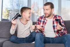 Father and son playing with joysticks. Excited little boy and confused father playing with joysticks at home Royalty Free Stock Images