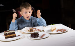 Excited little boy eyeing a choice of cakes Stock Images
