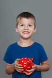 Excited little boy holding piggy bank Stock Images