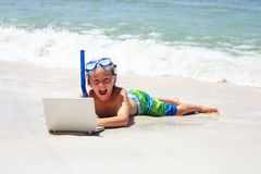 Excited little boy lying on beach with laptop Royalty Free Stock Image