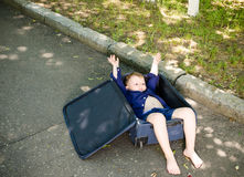 Excited little boy lying in a suitcase cheering Royalty Free Stock Photography