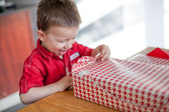 Excited little boy opening his birthday gift Royalty Free Stock Images