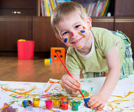Excited little boy painting. With colorful paints Royalty Free Stock Images