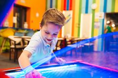 Excited little boy playing air hockey. At Arcade centre Royalty Free Stock Photo