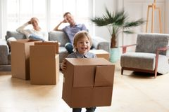 Excited little boy playing with cardboard box on moving day. Parents relaxing on sofa while their happy active son enjoying packing relocating into new home Stock Photography