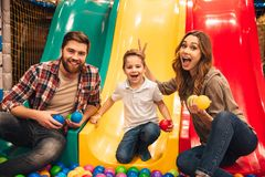 Excited little boy playing on a slide with his parents. At Arcade centre Stock Photo