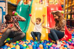 Excited little boy playing on a slide. With his parents at entertainment centre Royalty Free Stock Photos
