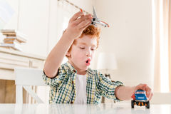 Excited little boy playing with toys at home Stock Photos