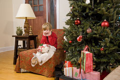 Excited little boy with present by Christmas tree Royalty Free Stock Photos