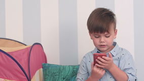 Excited little boy reading a message on his phone stock video