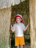 Excited little boy in a reed hut Stock Photo