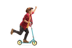 Excited little boy riding a scooter and gesturing with his hand. Full length portrait of an excited little boy riding a scooter and gesturing with his hand Royalty Free Stock Image