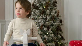 Excited little boy riding wooden rocking horse near the Christmas tree stock video footage