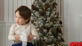 Excited little boy riding wooden rocking horse near the Christmas tree. Closeup shot. Professional shot on Lumix GH4 in 4K resolution. You can use it e.g. in Stock Photography