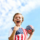 Excited little boy screaming holding rugby ball. Portrait of excited little boy wearing t-shirt with stars and stripes holding rugby ball, looking at camera and Stock Images