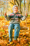 Excited little boy on a swing outdoor. Autumn leaves on background Royalty Free Stock Photo