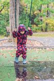 Excited little boy on a swing outdoor, autumn leaves on backgrou Stock Photos