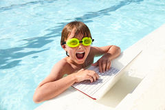 Excited little boy using laptop in swimming pool Stock Photos