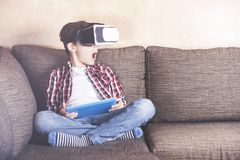 Boy experiencing virtual reality. Excited little boy using tablet and headset reacts while experiencing virtual reality at home Stock Image