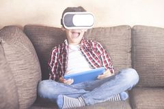 Boy experiencing virtual reality at home. Excited little boy using tablet and vr headset reacts while experiencing virtual reality at home Stock Images