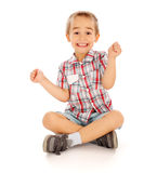 Excited Little Boy. Very excited little guy sitting and cheering Royalty Free Stock Photography