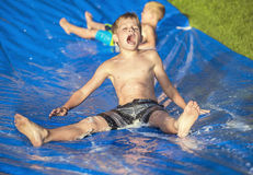 Excited little boys playing on a slip and slide outdoors Royalty Free Stock Photography