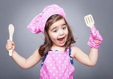 Excited little cook. Posing with open moth and spoons in her hands Royalty Free Stock Photography