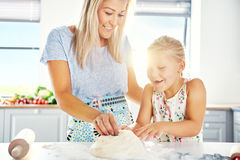 Excited little girl helping her mother make pastry Royalty Free Stock Photos