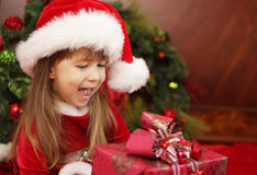 Excited little girl looking at christmas present Royalty Free Stock Photos