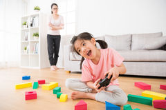 Excited little girl playing joystick video game. With colorful blocks toys scattered in living room wood floor and unhappy mom standing at rear angrily looking stock image