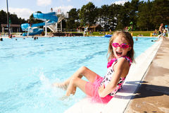 Excited little girl screaming sitting on pool edge Stock Image