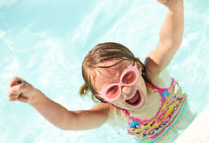 Excited little girl shouting in pool raising arms. Portrait of excited little girl wearing sunglasses swimming in pool, looking at camera and shouting raising Stock Photos