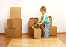 Excited little girl unpacking in her new home Stock Photo