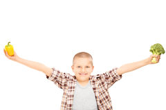 An excited little kid holding broccoli, and a pepper in his hand Royalty Free Stock Photo
