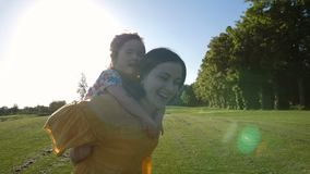 Excited girl laughing on mother`s back in park stock footage