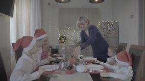 Excited lovely happy family of six celebrating Christmas dinner in festive atmosphere cozy kitchen. Happy lovely excited family of six celebrating Christmas stock video footage