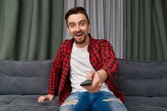 Excited male changing channels on TV. Attractive bearded guy in casual outfit using remote control to change channels while sitting on comfortable couch and stock photography