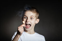 Excited male child yelling with flaming match. Excited wide eyed male child wearing white shirt yelling with flaming match against a black background Royalty Free Stock Photo