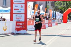 Excited male runner crossing the finshline of a marathon. ODESSA, UKRAINE - 25 JUN 2017: Excited male runner crossing the finshline of a marathon. Marathon Royalty Free Stock Images